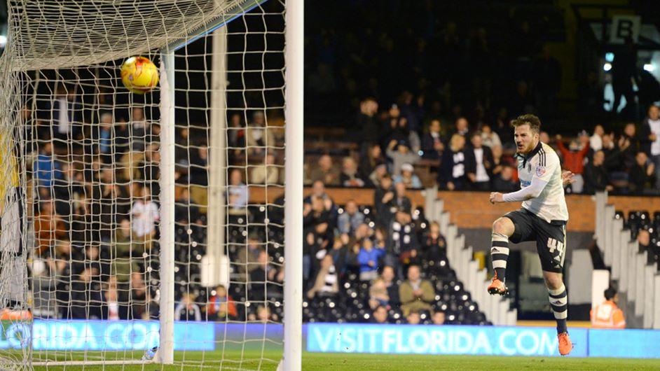 Footballer kicking ball into net